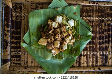 Siomay - Indonesian dish with steamed fish dumpling and vegetables served in peanut sauce in banana leaf, view from top.