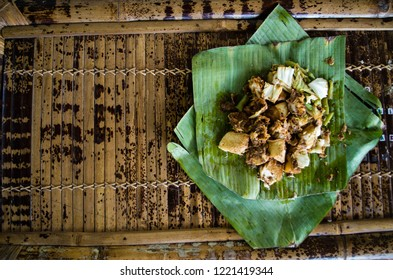 Siomay - Indonesian dish with steamed fish dumpling and vegetables served in peanut sauce in banana leaf - copy space left.