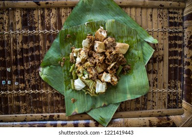 Siomay - Indonesian dish with steamed fish dumpling and vegetables served in peanut sauce in banana leaf - centered.