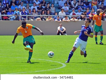 SION, SWITZERLAND - JUNE 4: Kolo toure of Ivory Coast kicks the ball in a friendly match against Japan for the 2010 world cup, Hasabe (17) chases:  June 4, 2010 in Sion Switzerland