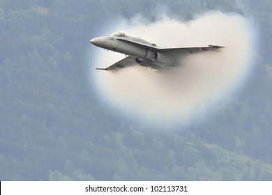 SION, SWITZERLAND - SEPTEMBER 17: Jet-plane breaks the sound barrier in front of the public during the Breitling Sion airshow on September 17, 2011 in Sion, Switzerland.