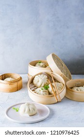 Siopao asado - filipino steamed buns with chicken filling (Cha siu bao) served on a grey background in bamboo steamer