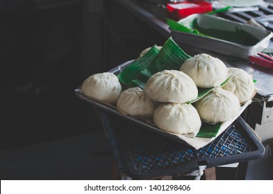 Siopao buns put in tray with banana leaf under buns