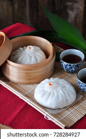 Siopao Chinese pork bun in bamboo container with tea on bamboo mat
