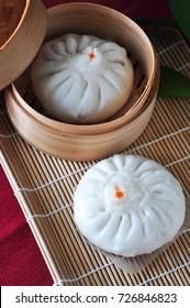 Siopao Chinese steamed pork bun in bamboo container put on bamboo mat