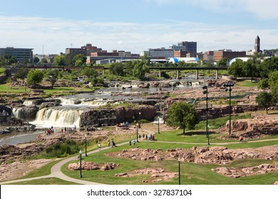 SIOUX FALLS, SOUTH DAKOTA, USA - AUGUST 8, 2015: Tourists visit Falls Park in Sioux Falls, South Dakota, USA with city skyline in the background on August 8, 2015.