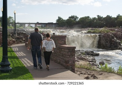 SIOUX FALLS, SOUTH DAKOTA/UNITED STATES - AUGUST 14: An unidentified couple strolls hand in hand by the waterfalls on August 14, 2017 in Sioux Falls, South Dakota.