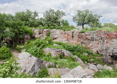 Sioux quartzite rock outcrop with trees and scattered boulders.