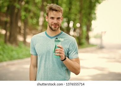 Sip of freshness after great workout. Man with athletic appearance holds bottle with water. Athlete drink water after training in park on sunny day. Man athlete in sporty clothes drink water.