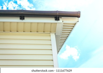 SIP panel house construction. Brown rain gutters. Drainage system with plastic siding and eaves on blue sky background.