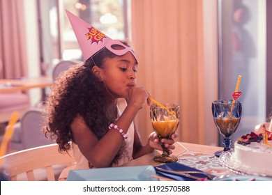 Sipping juice. Long haired girl thoughtfully looking at the juice while drinking it through sipping straw