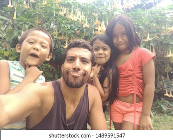 Siquijor, Philippines - May, 2019: A western young man selfie with small Filipino kids on the island of Siquijor, in the Visayas region.