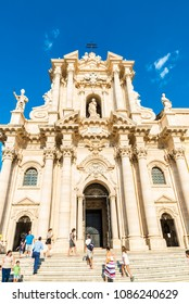 Siracusa, Italy - August 17, 2017: Facade of the Cathedral of Siracusa with people around in the old town of the historic village of Siracusa in Sicily, Italy