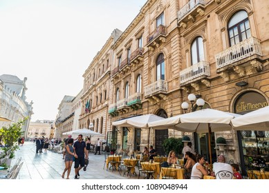 Siracusa, Italy - August 17, 2017: Terrace of a restaurant bar with people around on a street in the old town of the historic city of Siracusa in Sicily, Italy