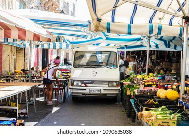 Siracusa, Italy - August 17, 2017: Van passing between fruit stalls in the food street market with people around in the old town of Siracusa in Sicily, Italy