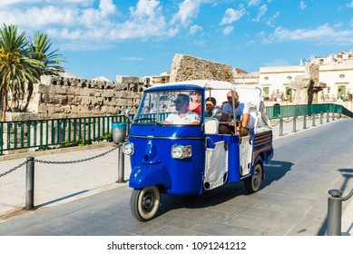 Siracusa, Italy - August 17, 2017: Family on a blue tricycle of the Piaggio brand that make tourist circuits on a street in the old town of Siracusa in Sicily, Italy