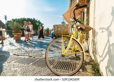 Siracusa, Italy - August 17, 2017: Old retro yellow bicycle parked on a street with people around in the old town of the historic city of Siracusa in Sicily, Italy
