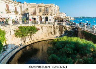 Siracusa, Italy - August 17, 2017: Promenade and fountain of Arethusa ( Fonte Aretusa) with people around in the old town of the historic city of Siracusa in Sicily, Italy