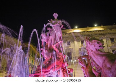 SIRACUSA, ITALY - JULY 17, 2019: Night view of the colorful and illuminated Diana's fountain in Piazza Archimede in Syracuse, Sicily Italy.
