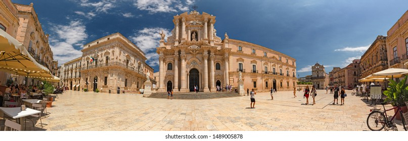 SIRACUSA, ITALY - JULY 18, 2019: Some tourists are walking admiring the baroque cathedral in the historic center of the island of Ortigia in Syracuse, in Sicily, Italy.