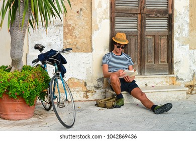 Siracusa, Italy - September 28, 2017: Man sitting and reading in an ancient street in Siracusa, Sicily, Italy