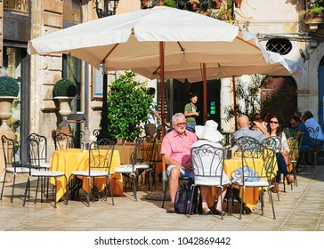 Siracusa, Italy - September 28, 2017: Senior couple at cozy street cafe in Siracusa, Sicily, Italy