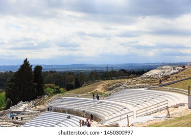 Siracusa, Sicily, Italy - May 01, 2019: Tourists walks by Teatro Greco, Greek amphitheater steps in Siracusa, spring sunny day