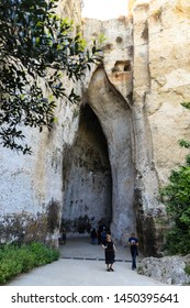 Siracusa, Sicily, Italy - May 01, 2019: tourist in the entrance of the cave Ear of Dionysius in Siracusa, natural acoustic miracle