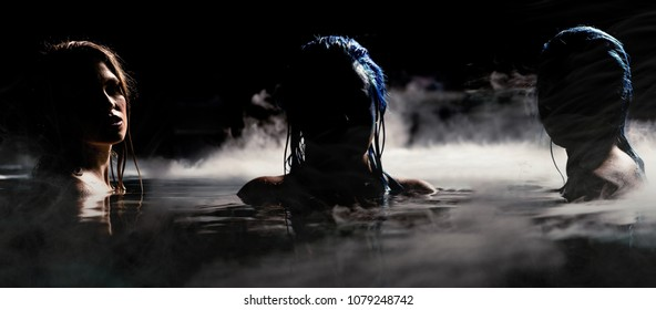 Sirens of the Night. Two mysterious sirens in fog covered water. Night scene with female models. Bright blue hair and custom mermaid makeup bring this nighttime scene to life.
