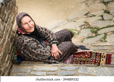 SIRINCE, TURKEY - APRIL 5, 2014 : Portrait of a old Turkish woman on the street in traditional clothing, while sit by her town  in the Sirince, Turkey