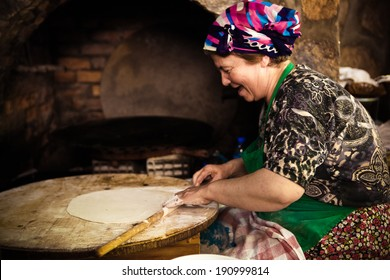 SIRINCE, TURKEY - MAY 24: Woman cooks a traditional Turkish pancake on May 24, 2011 in Sirince, Turkey