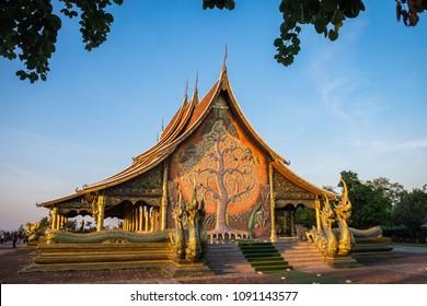 Sirindhornwararam Phu Prao temple - Ubon Ratchathani, Thailand in the evening with leaves in foreground. Kalpapruek tree (Cassia Bakeriana) with green phosphor lighten in the dark as landmark.