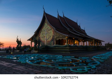 Sirindhornwararam Phu Prao temple - Ubon Ratchathani, Thailand in twilight moment. Kalpapruek tree (Cassia Bakeriana) with green phosphor lighten in the dark as landmark for tourist to visit.