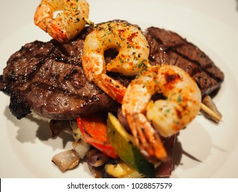 Sirloin steak and grilled shrimps on a white plate