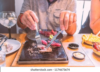 sirloin steak on a very hot stone being cooked by a man to his own taste on a wooden table with a knife and fork