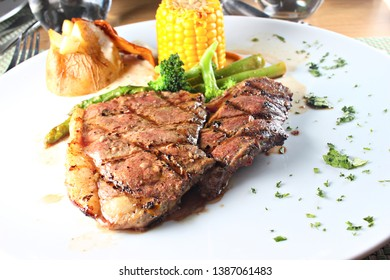 Sirloin steak served with vegetables on a white plate, shallow focus
