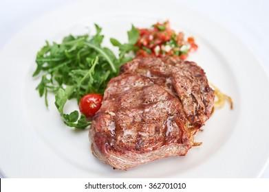 Sirloin steak with tomato tartare on white plate studio shot