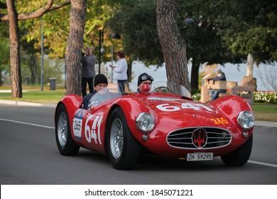 Sirmione, Brescia, Italy - 22 October 2020: 1000 mille miglia 2020. Red retro cars, Maserati, 265, 641. Mille Miglia on Lake Garda, Sirmione. The Mille Miglia was a public road endurance race.