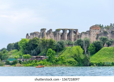 Sirmione, Italy - April 29, 2018: Amazing panoramic view of Grotte di Catullo from the Garda Lake. The ruins of a Roman villa and Stony Beach. Ancient Roman archaeological site in Sirmione.