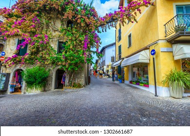 SIRMIONE, ITALY - AUGUST 28, 2017: Amazing colorful purple bougainvillea flowers around the windows. Promenade with souvenir shops in Sirmione, Italy, Europe AUGUST 28, 2017 in Sirmione, Italy