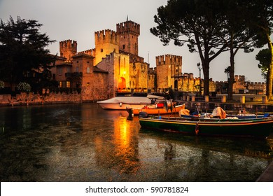 Sirmione, Italy. Illuminated Scaliger Castle in Sirmione, Italy - the main attraction of the region at night with reflection in the water