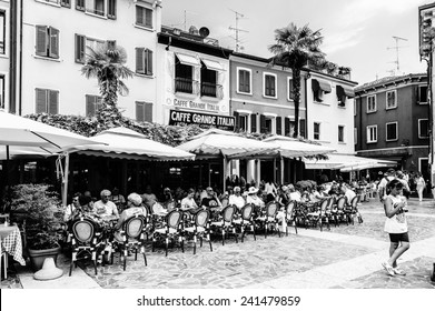 SIRMIONE, ITALY - JUNE 26, 2014: Street restaurant in the Sirmione town, Italy. Sirmione became popular touristic destination on the Lake garda, the largest lake in Italy