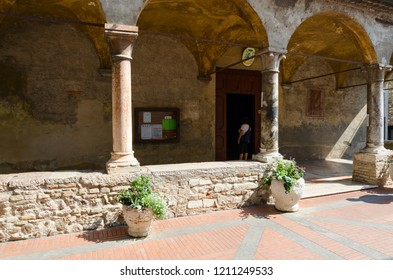 SIRMIONE, ITALY - SEPTEMBER 16, 2018: Unknown woman is at entrance to Church of Santa Maria Maggiore (XV century) on narrow street in historic center of Sirmione, Italy