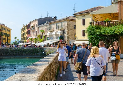 SIRMIONE, ITALY - SEPTEMBER 16, 2018: Unidentified tourists walk in historic center of resort town of Sirmione on shore of Lake Garda, Italy