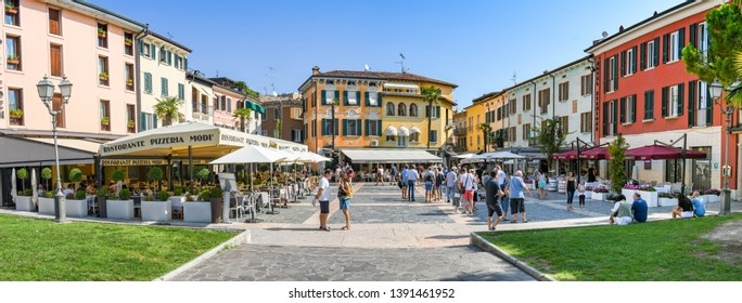 SIRMIONE, LAKE GARDA, ITALY - SEPTEMBER 2018: Panoramic view of people in the square near the harbour in Sirmione on Lake Garda. Around the square are restaurants and hotels.