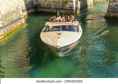 SIRMIONE, LAKE GARDA, ITALY - SEPTEMBER 2018: Visitors to Sirmione on Lake Garda taking a trip around the moat of Scaliger Castle in a motor launch,