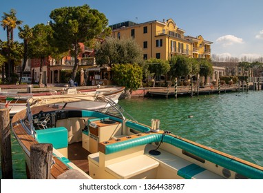 Sirmione, Lombardy / Italy - March 08 2019: A vintage speedboat moored at a pier on the shore of Lake Garda with the Hotel Sirmione and the lakefront in the background