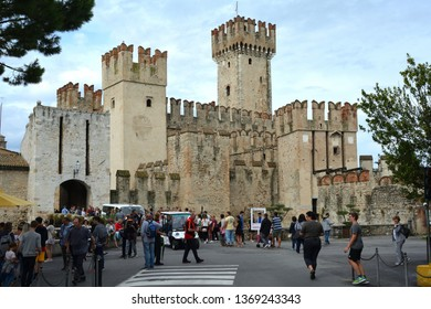 Sirmione, Lombardy, Italy - September 05, 2018: Tourists in front of the Scaligero castle in the historic center of Sirmione on Lake Garda - Italy.