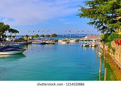 Sirmione,Lombardy,Italy-July 19 2018:Tour boat port by the historic landmark Rocca Scaligera fortress in Sirmione town-beautiful historic town resort on Garda Lake