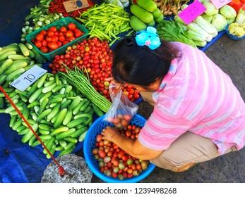 SISAKET, THAILAND – SEPTEMBER 24, 2018 Woman seller vegetable in Katthalak Market in Sisaket Thailand. Traveling in Sisaket Thailand.